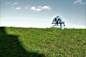 Industriële blauwe pijpen in gras met wolkenlucht van Maud De Vries
