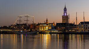 Kampen gedurende zonsondergang met de IJssel, grote zeilschepen en de kerktoren.