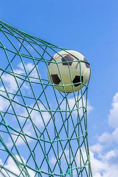 Voetbal in goal net met blauwe lucht van Ben Schonewille
