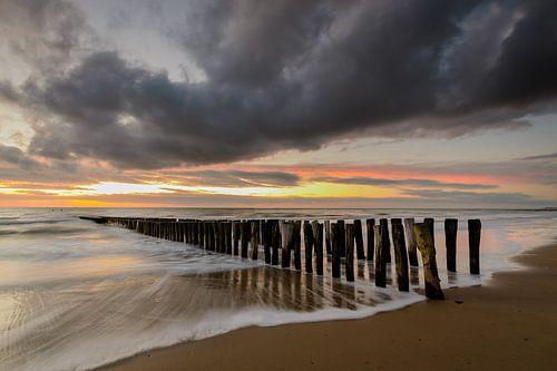 Paalhoofden op het strand na zonsondergang van
