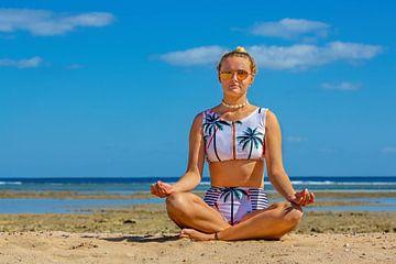 Jonge Nederlandse vrouw in bikini mediteert op strand van Hurghada in Egypte van Ben Schonewille