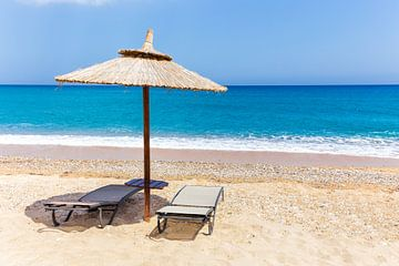 Strohschirm mit zwei Sonnenliegen am Sandstrand mit blauen Meer in Griechenland von Ben Schonewille
