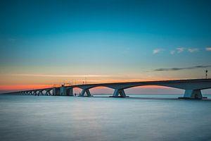 De welbekende Zeelandbrug in Nederland tijdens de zonsondergang. van