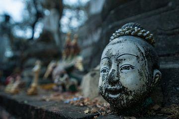 Oud verweerd lachend hoofd van Thais boeddhabeeld op altaar bij tempel van Thijs van Laarhoven