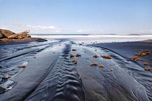 Dunkler Strand mit Sandrippen von