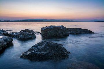 Rotsen in de zee met de warme tinten van de ondergaande zon. van Michel Geluk