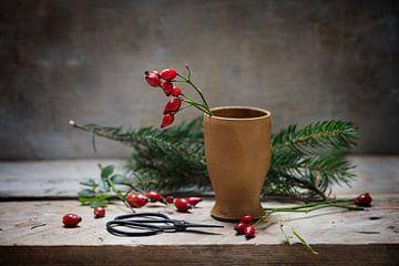 préparation d'une décoration de Noël naturelle avec des cynorhodons dans un vase en grès et des bran sur Maren Winter
