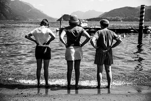 Fine art zwart-wit foto van drie vrouwen met handen in de zij uitkijkend over een meer in Italië