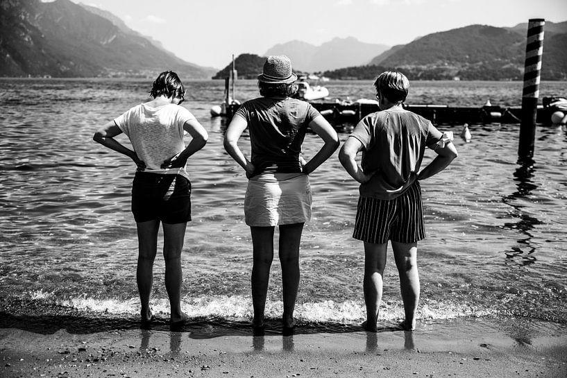 Fine art zwart-wit foto van drie vrouwen met handen in de zij uitkijkend over een meer in Italië van Monique Tekstra-van Lochem