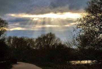 De zon die door de wolken schijnt. van Jurjen Jan Snikkenburg