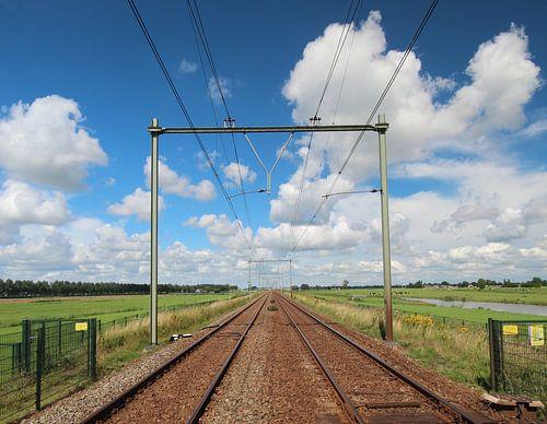 Bahnübergang mit unbegrenzter Schiene zum Horizont mit hellem blauem Himmel und weißen Wolken von