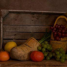 stilleven van een houten kistje met klompen en fruit van Compuinfoto .