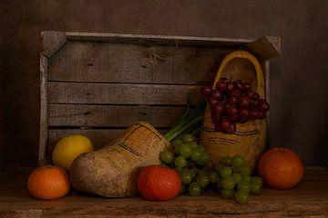 stilleven van een houten kistje met klompen en fruit