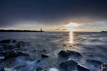 zee tegen rotsblokken met op de achtergrond een stenen golfbreker van Etienne Rijsdijk