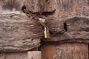 Een sterk vervallen deur, afgesloten met roestige ketting en een nieuw hangslot.