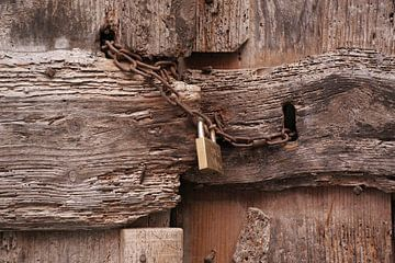 Een sterk vervallen deur, afgesloten met roestige ketting en een nieuw hangslot. van Gert van Santen