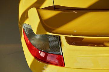 Zon en schaduwlijnen op de spoiler van een gele Porsche 91 GT2. van Xander Verweij