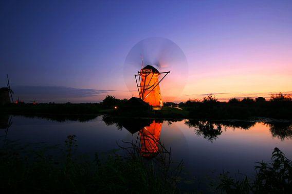 Kinderdijk molen bij ondergaande zon. Tijden de verlichte week met draaiende wieken