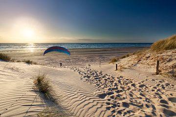 Mann Gleitschirmfliegen am Strand bei Sonnenuntergang über dem Meer im Sommer von Olha Rohulya