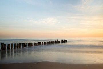 Paaltjes in zee bij zonsondergang van Barbara Brolsma