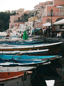 Gekleurde vissersbootjes in de haven van Procida met de boulevard op de achtergrond van Michiel Dros