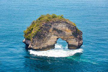Wilde rotsboog in de zee op Nusa Penida in Indonesië van Michiel Ton
