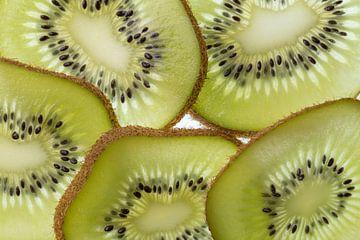 Meerdere plakken van een doorgesneden Kiwi vrucht in tegenlicht opname van Tonko Oosterink