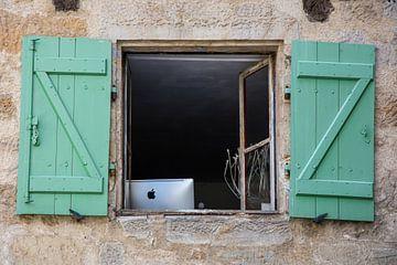 Un iMac Apple derrière une fenêtre avec des volets verts sur Wil Wijnen