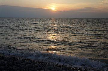 Prachtige zonsondergang aan een kiezelstrand van Sandra van der Burg