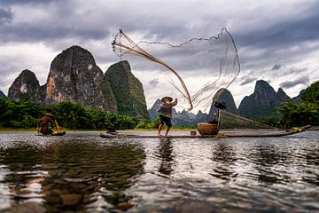 Vissen met aalscholver in China van Michael Bollen