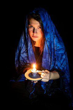 Traurige junge Frau mit Kerze und blauem Kopftuch von Hans-Jürgen Janda
