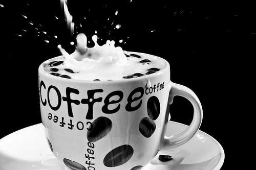 Vallende koffiebonen in een koffie tas met melk van