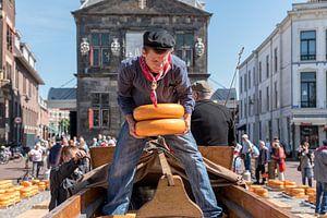 Jongen sjouwt kazen op de Kaasmarkt in Gouda