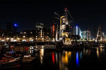 Rotterdam met in de haven de verlichte zandzuiger.