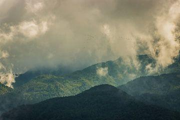 Zonsondergang in de bewolkte bergen van Maarten Borsje
