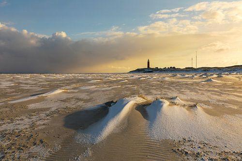 Besneeuwd strand met rode vuurtoren van