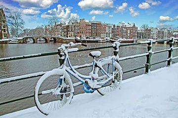 Besneeuwde fiets aan de Amstel in Amsterdam in de winter van Nisangha Masselink