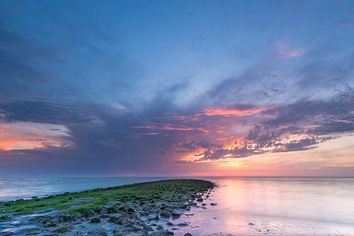 Zonsondergang Noordzee met donkere wolken en strekdam