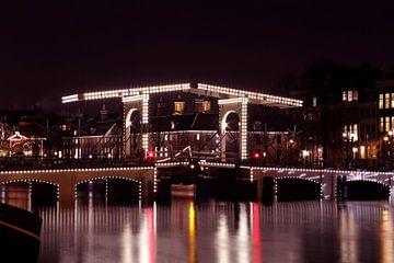 Stadsbeeld van Amsterdam aan de Amstel met de Magere Brug bij zonsondergang in Nederland van Nisangha Masselink