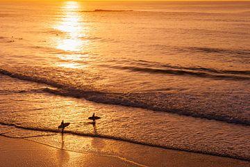 Surfers bij zonsondergang op strand in de Algarve, Portugal van Chris Heijmans