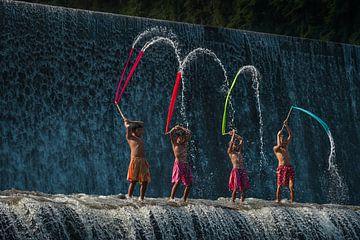 Balinesische Jungen spielen mit bunten Tüchern auf dem Tukad-Unda-Wasserdamm in Bali von Anges van der Logt