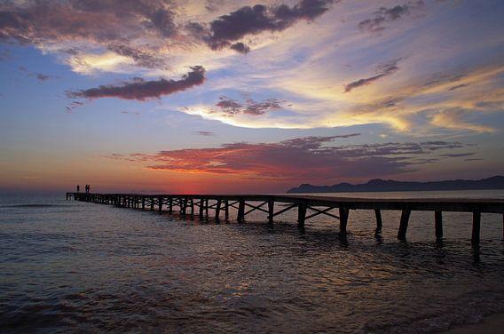 Vissers op de pier in de zee bij zonsopgang