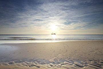 Vissersboot vaart voor de zon langs tijdens zonsondergang aan het strand van Gerben van Dijk