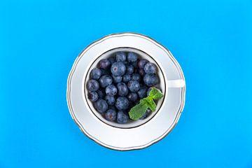 Blauwe bessen in een witte kop op schotel tegen blauwe achtergrond. van Ans van Heck