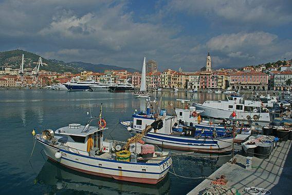 Een haven vol jachten en bootjes met stadje Imperia op achtergrond.
