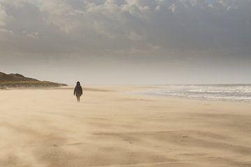 Dame op stormachtig strand van Laura Loeve