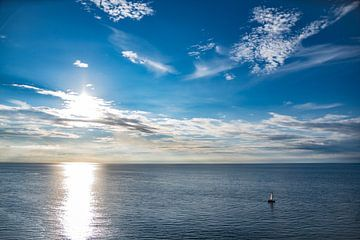 Zeilboot in een verlaten oceaan met een zonsondergang van Jan Hermsen
