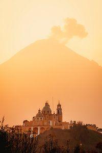 Kerk en vulkaan met wolken tijdens de warme, oranje, zonsopkomst in Mexico van Maartje Hensen