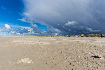 Strand van Terschelling met stormachtige wolken in blauwe lucht van Sander Groffen