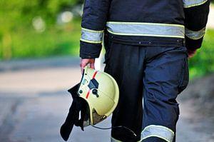 Brandweerman loopt met helm van